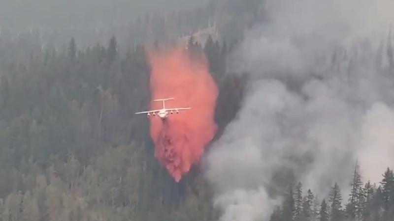 消防飛機在兩哩路的上空向山火現場投灑阻燃劑。加拿大皇家海上搜救隊