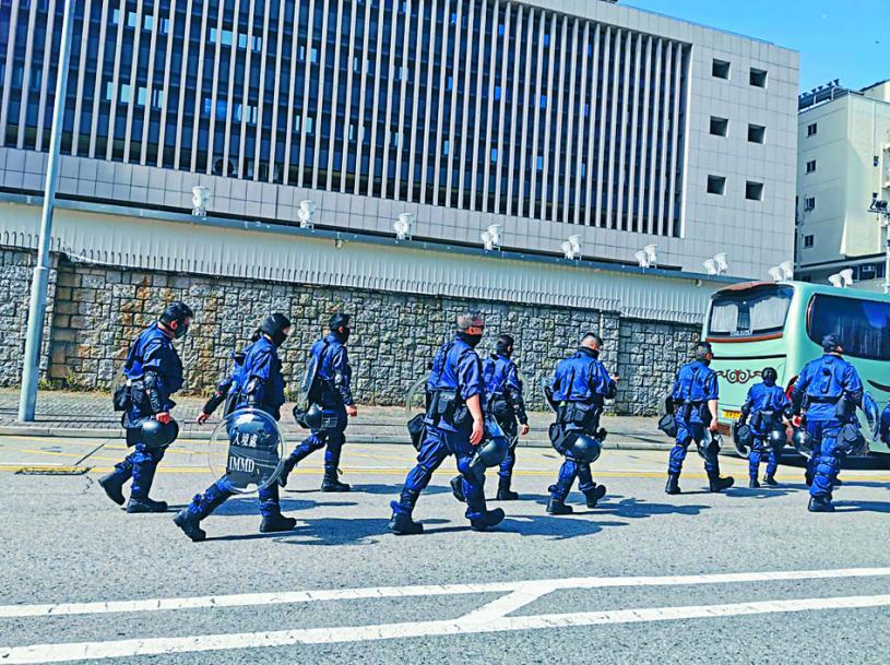■由入境處人員擔任的特務警察,昨日步出政府總部開始執勤時,均配備防暴裝備如護甲、盾牌等。本報記者攝