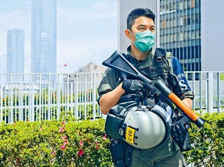 駐守政府總部的特務警察持防暴槍戒備。