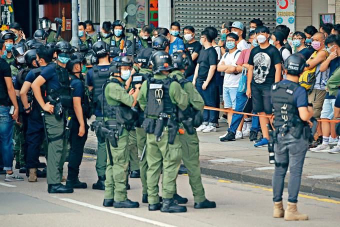 警方在彌敦道截查多名可疑人士,防止非法聚集。