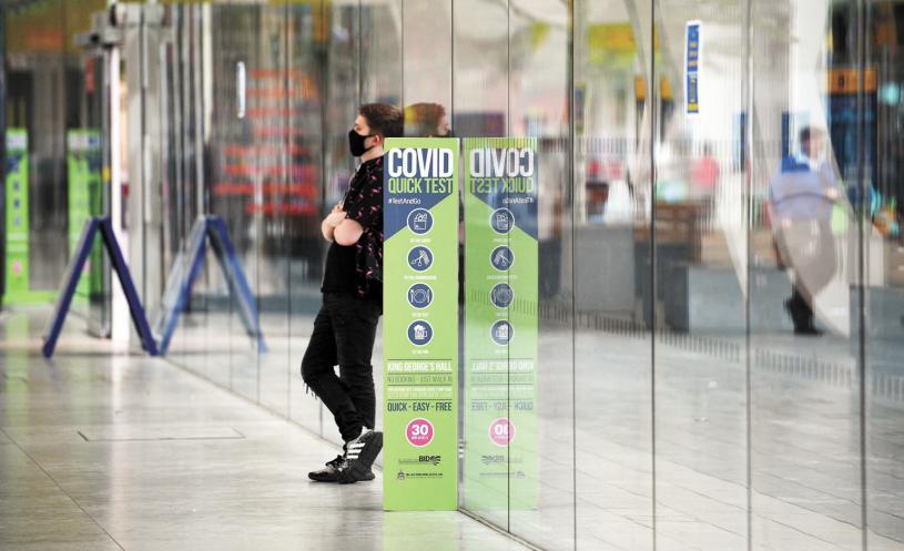 英格蘭過去一星期新增逾3.3萬人感染Delta變種病毒,為此,當局延遲解封,圖為一名戴口罩的男子站在公交站附近的Covid-19信息標誌旁。法新社