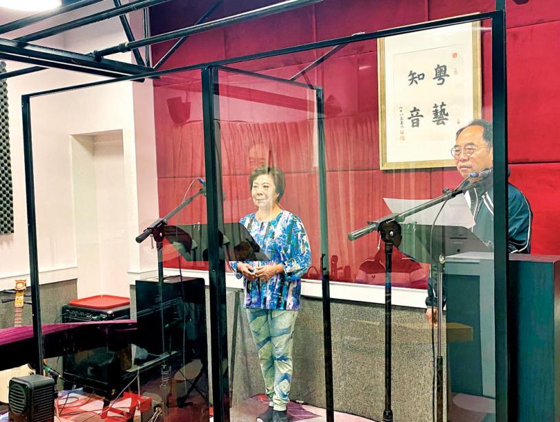 ■粵劇社成員吳慧明(左)與周鍵棠(右)在有機玻璃屏後的舞台上演唱。