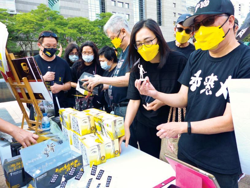 ■多伦多香港家长组发言人谢先生向市民介绍义卖物品。本报记者摄