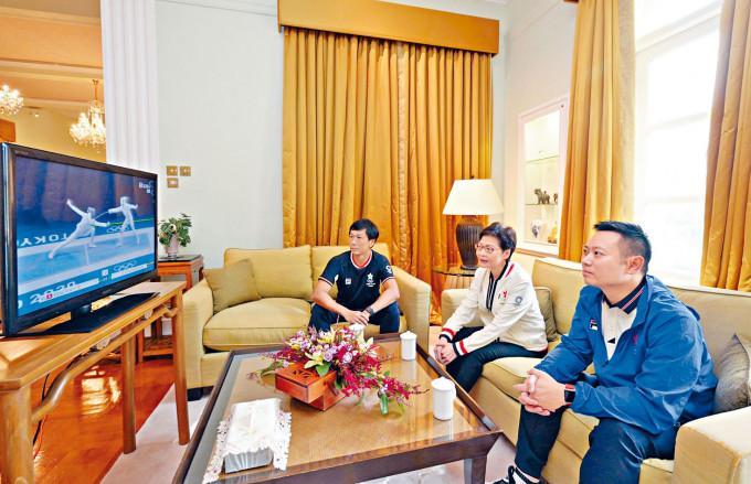 特首林鄭月娥與民政事務局局長徐英偉(右)、體育專員楊德強在電視機前,為香港運動員打氣。