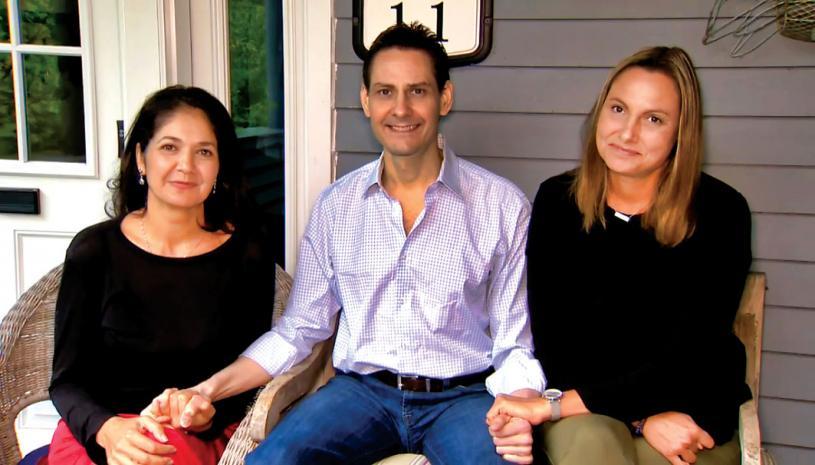 ■康明凱(中)在回到多倫多後,星期日與妻子納吉布拉(左)及妹妹波莎(右)於後者家中,接受電視訪問。Global
