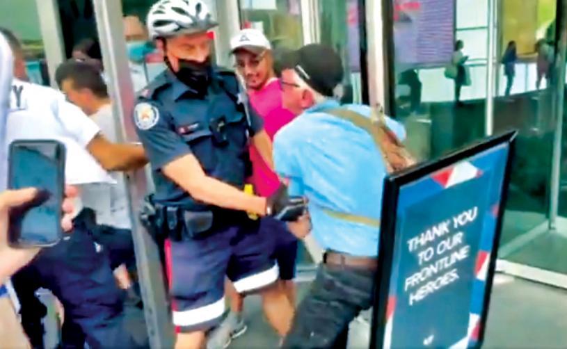 ■一群反對疫苗示威者企圖進入多倫多市伊頓中心,被警方及保安員阻止。 CP24