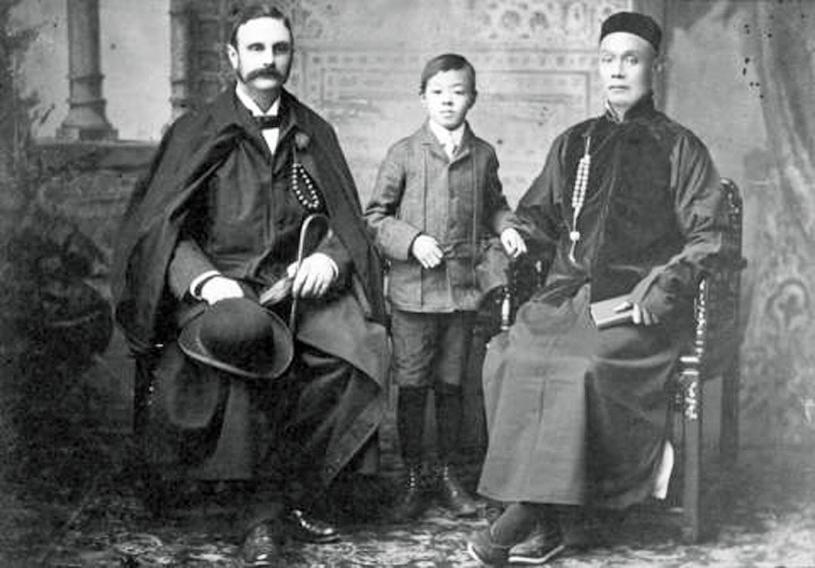 身穿唐裝的陳才(右),1910年與不知名歐裔人士及男童合照。 溫哥華檔案館