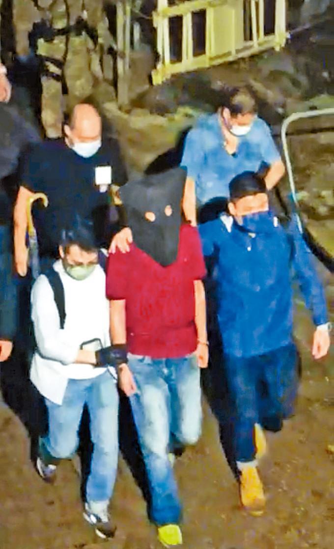 身穿紅衣的疑兇蔡南生,昨晚在南丫島落網後由多名人員押走。小圖:警方昨日發放疑兇蔡南生第二張照片。