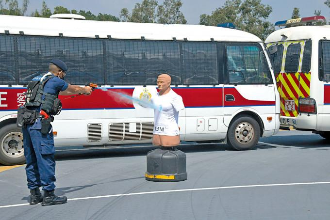 示範人員向目標人偶使用胡椒水發射器,可見射出一道藍色水柱。
