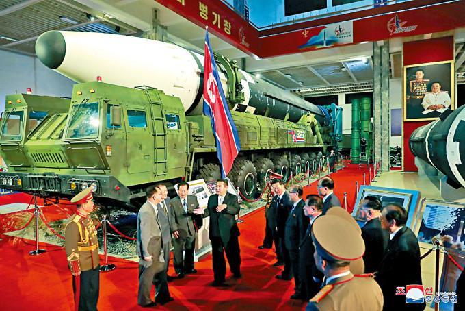 金正恩於武器展場上與官員交談。